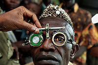 A man has his eyesight tested by a member of ophthalmologist Doctor Richard Hardi's team in the remote village of Pania. <br /> <br /> From his base in Mbuji Mayi Hungarian ophthalmologist Friar Richard Hardi and his team travelled deep into the Congolese rainforest, by 4x4 and canoe, to treat people in isolated communities most of whom have never seen an ophthalmologist. At a small village called Pania they established a temporary field hospital and over the next three days made hundreds of consultations. Although both conditions are preventable, many of the patients they saw had Glaucoma or River Blindness (onchocerciasis) that had permanently damaged their eyesight. However, patients with cataracts, a clouding of the eye's lens, who were suitable for treatment were booked for an operation. For two days the team carried out the ten minute procedure on one patient after another. The surgery involves making a 2.2mm incision into the remove the damaged lens that is then replaced by an artificial one. Doctor Hardi is one of the few people willing to make such a journey but is inspired to do so by his faith and, as he says: 'Here I feel that I can really make a difference in people's lives'. /Felix Features
