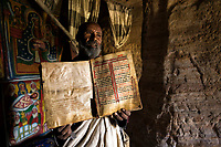The priest of Mikael Melehayzenghi rock hewn church shows his Ge'ez bible.