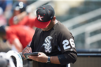Kannapolis Intimidators hitting coach Jamie Dismuke (26) makes notes during the game against the Greensboro Grasshoppers at Kannapolis Intimidators Stadium on August 5, 2018 in Kannapolis, North Carolina. The Grasshoppers defeated the Intimidators 2-1 in game one of a double-header.  (Brian Westerholt/Four Seam Images)