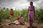 CHENNAI, INDIA, JULY 2012: .Lakshmii mother of Rajeswuri 9 years old and Sampoornum, 12 years old, july 2012..After she got pregnant with the third daughter she was pushed by the family to make infanticide. She gave her third doughter poisoned milk and then burried her behind her home..Here posing for a portrait on the graveyard of her third daugheter. Female infanticide is the intentional killing of baby girls due to the preference for male babies and from the low value associated with the birth of females.In rural India, the centuries-old practice of female infanticide can still be considered a wise course of action. © Giulio Di Sturco
