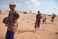 Somali refugees in Dadaab refugee camp carry their sick and malnourished children to a new feeding center run by MSF at the outskirts of the sprawling refugee camp.