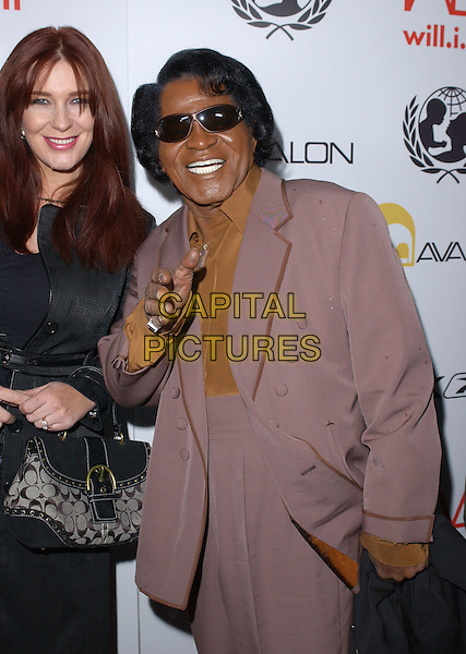 TOMMIE RAE & JAMES BROWN.Will.i.am Music Group and RBK's Tsunami Relief Benefit Concert held at Avalon in Hollywood, California .February 11th, 2005.half length sunglasse shades married husband wife purple suit jacket brown trim hand gesture.www.capitalpictures.com.sales@capitalpictures.com.Supplied By Capital PIctures