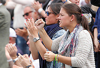 Italian tennis player Flavia Pennetta (L) applauds her boyfriend Italy's Fabio Fognini during his Davis Cup quarter-final tennis match against Britain's Andy Murray in Naples April 6, 2014.