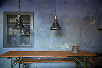 A retro pendant lamp hangs above an old school-room table and benches in a rustic kitchen. A small storage cupboard is recessed into the stone wall, which has a simple blue colour wash.