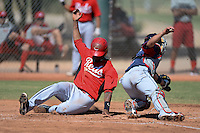 Cincinnati Reds outfielder Gabriel Rosa (50) slides home past catcher Tony Wolters during an instructional league game against the Cleveland Indians on September 28, 2013 at Goodyear Training Complex in Goodyear, Arizona.  (Mike Janes/Four Seam Images)