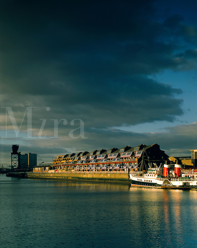 """Historic paddle-steamer the """"Waverley"""" under a dramatic evening sky, tied up alongside modern condominium apartments along the River Clyde, Glasgow, Scotland"""