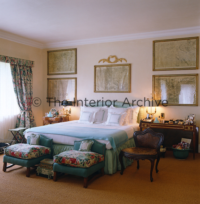 The bedroom has chintz curtains with stools of matching fabric at the foot of the bed and the wall is decorated with a series of framed maps