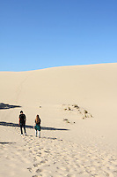 Teenagers follow the footsteps of others up the sand dunes at Oregon Dunes National Recreation Area