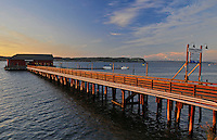 Historic Coupeville Wharf on Penn Cove, highlighted by sunset with Mt Baker backdrop. Coupeville, Ebey's Landing National Historical Reserve, Whidbey Island, WA