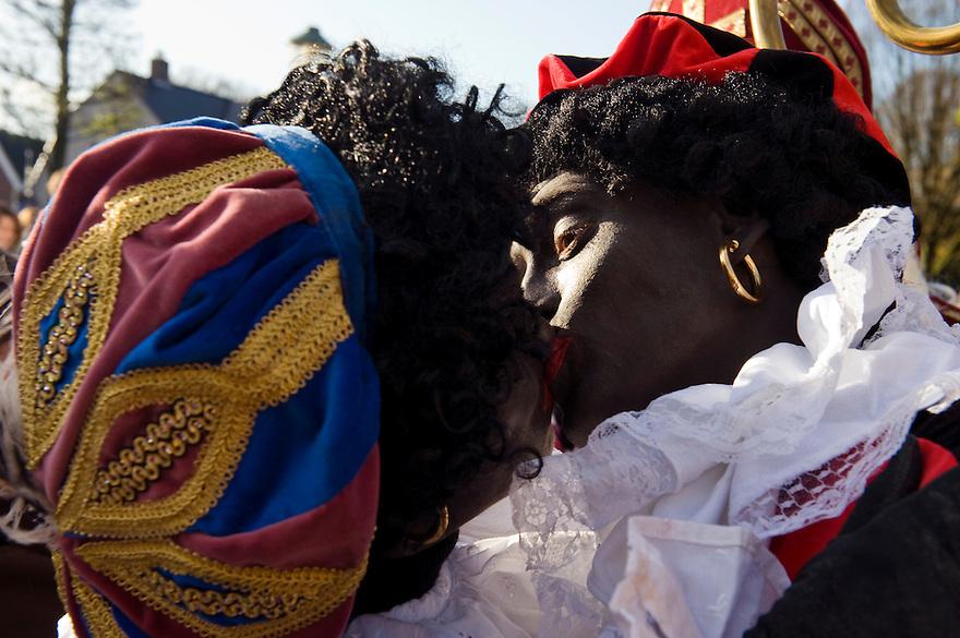Nederland, Doorn, 14 nov  2009.Intocht Sinterklaas in Doorn.Zwarte Pieten zoenen met elkaar tijdens de intocht. ..Foto (c) Michiel Wijnbergh
