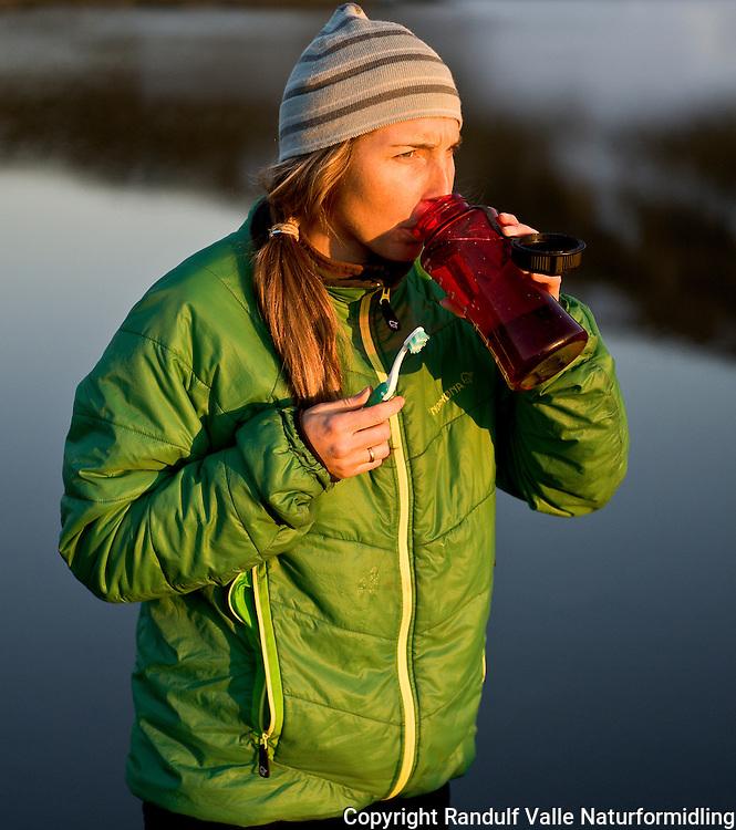 Dame pusser tenner en vårkveld i Finnmark. ---- Woman brushing teeth.