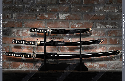 Samurai sword set Japanese Katana Wakizashi and Tanto blades in scabbards on a grungy brick wall background
