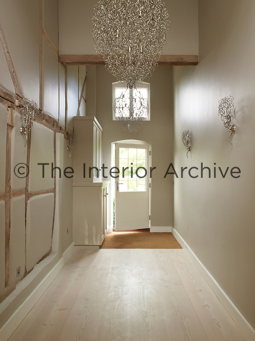 White ash floorboards light up the entrance hallway in this converted manor house