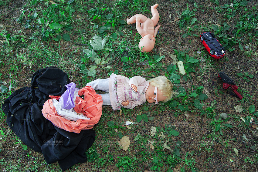 Italy. Lombardy Region. Como. Homeless african migrants living in the park below the San Giovanni railway station. Two red toys cars, two dolls and some used clothes are lying on the grass. 11.08.2016 © 2016 Didier Ruef
