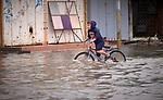 A boy rides a bicycle through a flooded street in war-torn Mosul, Iraq.
