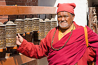Bodhnath, Nepal.  Buddhist Monk Turning Prayer Wheel.