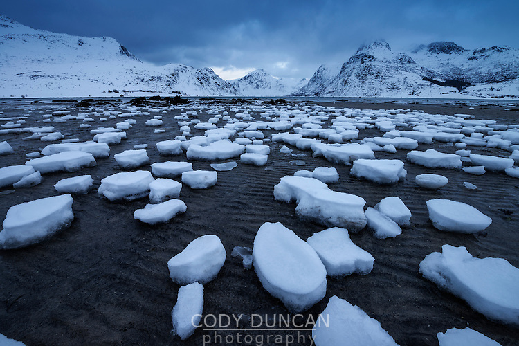 Snow patters on sand in Flakstadpollen at low tide, Flakstadøy, Lofoten Islands, Norway