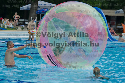 Child enjoys playing in an air sphere floating on the pool in bath Palatinus in Budapest, Hungary on August 06, 2011. ATTILA VOLGYI