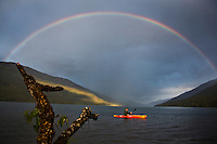 Darrell Trouton paddles a kayak as a rainbow stretches across the sky in Trout Lake, British Columbia on Tuesday May 28, 2013. THE CANADIAN PRESS/Jason Franson