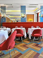 The original ceramic floor tiles have been used as a central element in the design of the dining room where large areas of mirrored wall are offset with inserts of the same cornflower blue