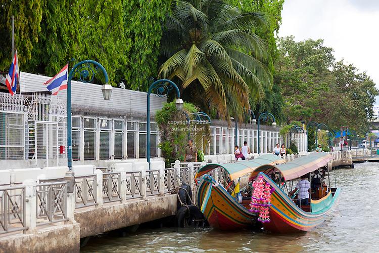 Longtail boats waiting for customers along the water wall along the Chao Praya River, Bangkok, Thailand