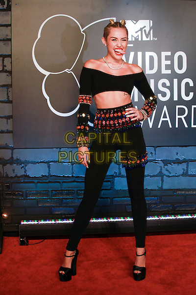 Miley Cyrus<br /> 2013 MTV Video Music Awards held at The Barclays Center, Brooklyn, New York, USA.<br /> August 25th, 2013<br /> VMA VMAS full length black top off the shoulder cropped trousers belly stomach midriff beads beaded embellished orange red green  hand on hip mouth open tongue hair up bunches buns <br /> CAP/ADM/MPI/C99<br /> &copy;C99/MPI/AdMedia/Capital Pictures