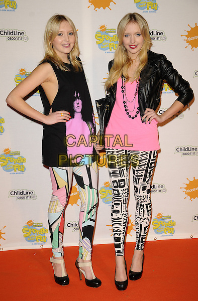 "SAM & AMANDA MARCHANT aka SAMANDA.At the ""Spongebob Squarepants - The Sponge who could Fly"" Gala performance at the Hammersmith Apollo, London, England. .March 5th 2009 .full length big brother twins sisters samantha patterned pucci style print leggings mulit-cooured graphic eighties leather cropped jacket face pink white top sleeveless tunic heels shoes hands on hips .CAP/CAN.©Can Nguyen/Capital Pictures."