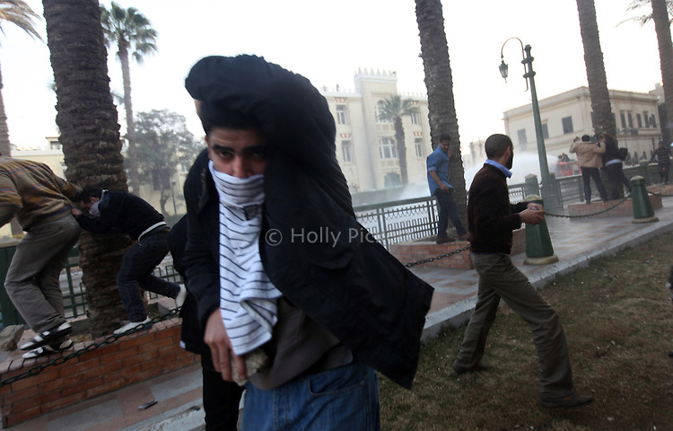 A protester with a rock turns away from police during a demonstration in downtown Cairo, Egypt, Jan. 25, 2011. The day was an official holiday in honor of the achievements of police, but thousands of demonstrators came out to protest corruption, unemployment and police torture.