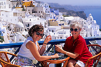 Tourist women having a drink on the cliffs of beautiful Santorini Greece on holiday