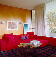 The bright-red L-shaped sofa seems to merge into the painted wall of David Netto's office