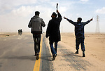Wielding knives and grenades, rebels marched closer to the city of Ajdabiya, Libya, March 24, 2011. Despite air strikes from Western war planes, which crippled Col. Muammar Qaddafi's military capability, the rebels seemed unable to advance and retake the city.