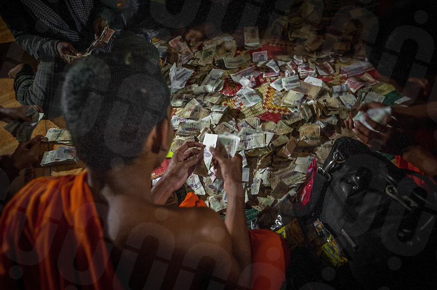 December 03, 2013 - Kampong Thom, Cambodia. Monks count the alms they recieved after the second day of walking during a 10-day Human Rights day march. © Luc Forsyth / Ruom