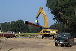 An electromagnetic head on the arm of a 360 degree excavator is used to unload the pipe and place it on the ground.