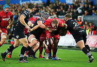 Samson Lee of the Scarlets (C) is held back by Scott Otten of the Ospreys (R) during the Guinness PRO14 Round 6 match between Ospreys and Scarlets at The Liberty Stadium , Swansea, Wales, UK. Saturday 07 October 2017