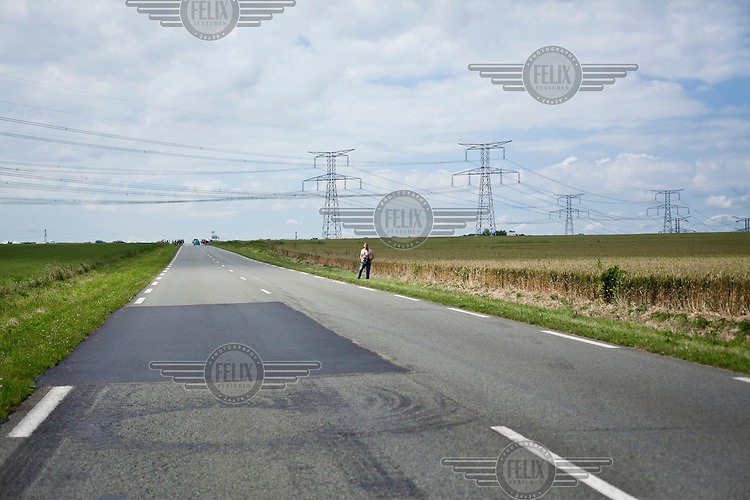 A man waits on the side of a road to see the Tour de France cycling competition pass through his village.