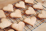 A collection of heart biscuits cooling on a baking tray