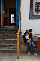 Blind Tibetan Headmaster Nyima Wangdu of the School for the Blind In Tibet cuddles his daughter Tenzin Dichen on the campus in the capital city of Lhasa, September 2016.