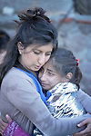 Zoya Hameed (left), a physician from the United Kingdom, hugs Hanin, a frightened Syrian refugee girl, on a beach near Molyvos, on the Greek island of Lesbos, on October 30, 2015. The girl was on a boat full of refugees that traveled to Lesbos from Turkey. The boat was provided by Turkish traffickers to whom the refugees paid huge sums to arrive in Greece. Hameed is one of hundreds of volunteers on the island who receive the refugees and provide them with warm clothing and medical care before they continue their journey toward western Europe.