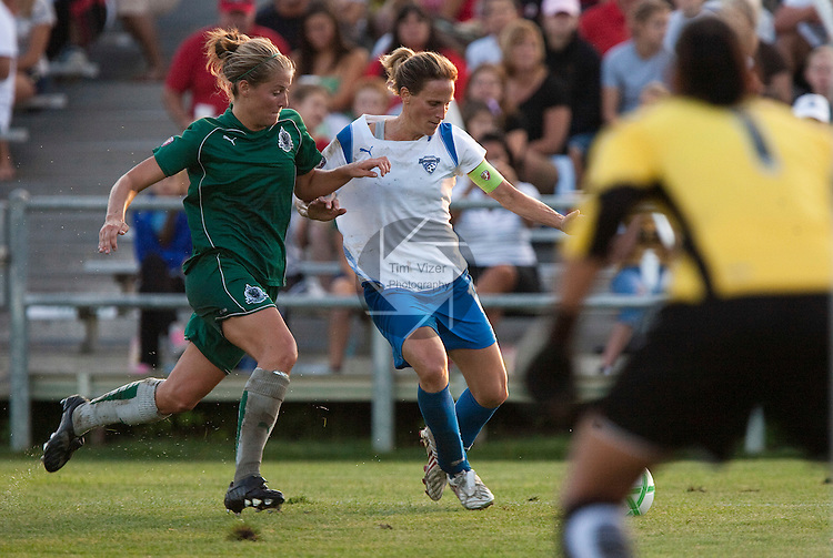 August 1 2009            Athletica's Elise Weber (12, left) and Breakers Captain Kristine Lilly (13, right) charge for the ball late in the first half.   At far right, back to camera, is Athletica goalkeeper Hope Solo, guarding the goal.   The St. Louis Athletica of the Women's Professional Soccer league hosted the Boston Breakers on Saturday August 1, 2009 at the Anheuser Busch Soccer Park in Fenton, Missouri.   The Athletica won, 1-0, and clinched a spot in the post-season playoffs...            *******EDITORIAL USE ONLY*******