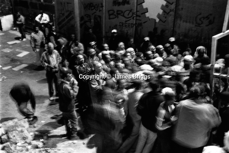 Palestinian labourers surge to get in line to enter checkpoint 300 in order to pass from Bethlehem to Jerusalem. 2007.