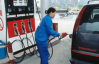 China. Province of Zhejiang. Hangzhou. A woman works as a pump attendant at a Sinopec gas station. She fills the tank of a Chevrolet van. Sinopec sells Shell petrol in China. © 2004 Didier Ruef
