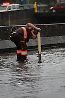 SAO PAULO, SP, 25/12/2013, ENCHENTE. Alagamento na Av do Estado, em decorrencia das fortes chuvas da tarde dessa quarta-feira (25).  Na foto agente do CET tenta desobistruir boca de lobo.LUIZ GUARNIERI/BRAZIL PHOTO PRESS.