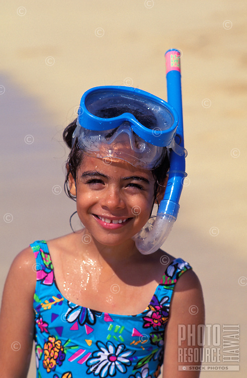 Little girl smiling and playing with snorkel mask on the beach at the north shore