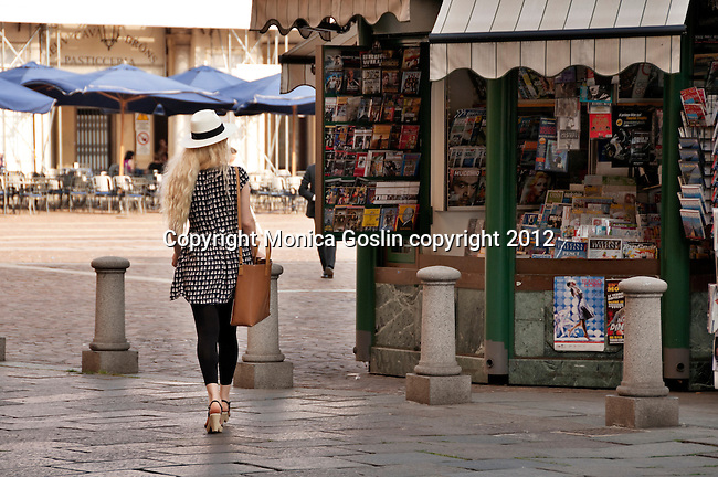 A girl wearing a straw hat walks by a newstand in the Piazza San Carlo in Turin, Italy