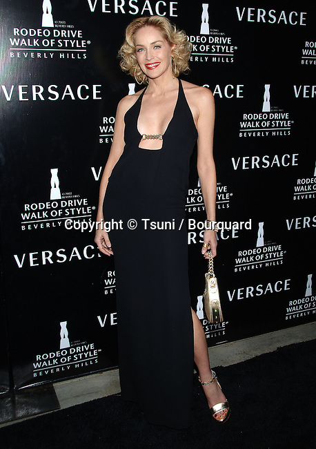Sharon Stone arriving at the WALK OF STYLE Awards to Versace at the City Hall in Beverly Hills.<br /> <br /> <br /> full length<br /> smile<br /> eye contact<br /> black dress