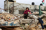 A Palestinian girl sits on the rubble of their destroyed house on a winter cold day, in Khan Youns southern in Gaza city January 20, 2020. Photo by Ashraf Amra