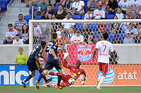 Edson Buddle (14) of the Los Angeles Galaxy beats New York Red Bulls goalkeeper Bouna Coundoul (18) to score during a Major League Soccer (MLS) match at Red Bull Arena in Harrison, NJ, on August 14, 2010.