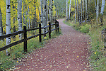 Red rock walking trail framed by split-rail fence and aspen, Telluride, Colorado, USA. John offers autumn photo tours throughout Colorado.