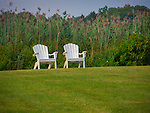 Adirondack chairs on lawn with sea grass.
