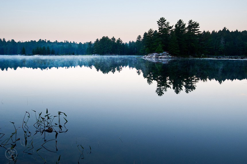 Dawn breaks over Balsam lake, with the far shore reflecting in the glassy still waters.